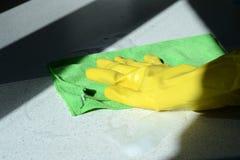 在橡胶太阳点燃的手套洗涤的表面的手 图库摄影