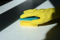 在橡胶太阳点燃的手套洗涤的表面的手 免版税库存照片