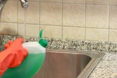 在橡胶手套的手与洗碗盘行为液体 免版税库存图片