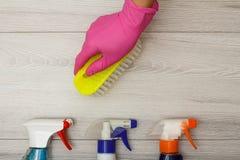 在橡胶手套藏品刷子的手与瓶在木背景的洗涤剂 免版税库存照片