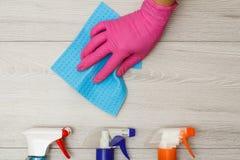在橡胶手套藏品餐巾的手与瓶在木背景的洗涤剂 免版税图库摄影
