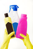 在橡胶黄色手套的手拿着三瓶在白色背景的液体洗涤剂 清洁 免版税图库摄影