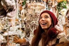 在橱窗购物圣诞树装饰前面的微笑的愉快的妇女 免版税图库摄影