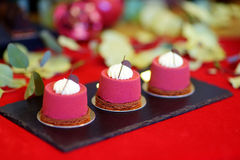 在欢乐事件点心桌上的三块可口红色天鹅绒杯形蛋糕  免版税库存图片
