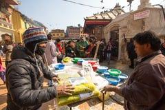 在欢乐庄严的Puja期间,在stupa Boudhanath附近供以人员捐赠的出售水泥的修理 库存照片
