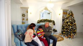 在欢乐心情的愉快和快乐的家庭获得乐趣并且一起笑,坐蓝色沙发在欢乐装饰的室 股票录像