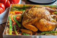 在欢乐烘烤形式薯类红萝卜芦笋葱草本罗斯玛丽麝香草金黄的外壳的自创烤被充塞的鸡菜 库存照片