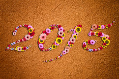 在欢乐的2015朵花在现代概略的灰泥后面的片段 免版税库存图片
