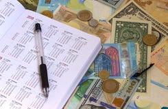 在欧元和美金、计算器、墨水笔和硬币金钱背景的日历 免版税库存图片