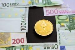 在欧元钞票旁边的Ethereum硬币在黑背景 数字货币,块式链市场 在隐藏硬币旁边的欧元票据 免版税库存图片