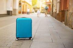 在欧洲城市街道,在欧洲拷贝空间的旅游业上的蓝色手提箱 库存图片