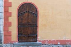 在欧洲成拱形与土气水泥黄色墙壁的老木门 免版税库存图片
