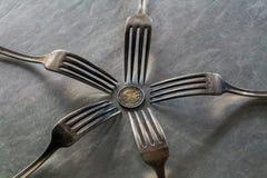 在欧洲硬币附近的五把叉子 免版税图库摄影