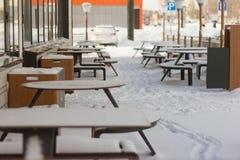 在欧洲部分的夏天咖啡馆在雪下 免版税库存照片