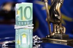 在欧盟旗子的手铐围拢的堆100欧元  免版税图库摄影