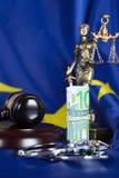 在欧盟旗子的手铐围拢的堆100欧元  免版税库存图片