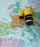 在欧洲和意大利的地图的黄色玩具照相机 库存照片
