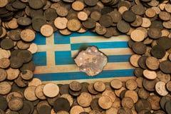 在欧洲硬币掠过的希腊旗子 库存照片