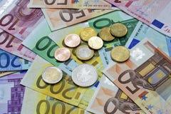 在欧洲笔记堆的欧洲硬币  免版税图库摄影