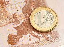 在欧洲钞票的一枚欧洲硬币 免版税库存图片