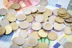 在欧洲钞票的欧洲硬币 免版税图库摄影