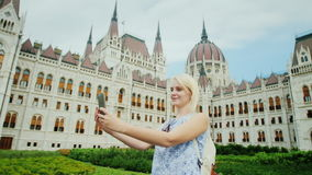 在欧洲附近的旅行-游人在布达佩斯做在匈牙利议会的背景的selfie 股票视频