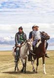 在歌曲Kul湖的马骑术在吉尔吉斯斯坦 库存图片