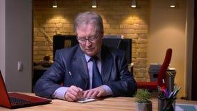 在正式服装的写笔记在笔记本轮给照相机和微笑的资深商人画象在办公室 股票录像