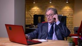 在正式服装的资深商人在笔记本的膝上型计算机和文字笔记前面谈话在手机在办公室 影视素材
