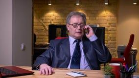 在正式服装的资深商人在膝上型计算机前面谈话殷勤地在手机在办公室 影视素材