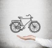 在正式白色衬衣的一只手拿着一辆速写的自行车的模型 在背景的混凝土墙 通勤或travellin的概念 免版税库存图片