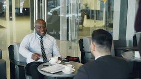 在正式衣裳的成功的非裔美国人的商人微笑和谈论财政报告与他的白种人 股票录像