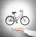 在正式衬衣的一只手拿着在墙壁上被画的一辆自行车 免版税库存图片