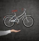 在正式衬衣的一只手拿着在黑黑板墙壁上被画的一辆自行车 库存图片