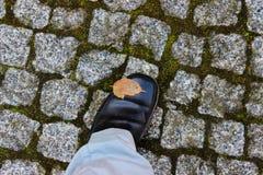在正式鞋子的一只脚在历史鹅卵石 免版税库存图片