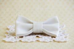 在正方形的米黄蝴蝶领带编织了在米黄背景的白色餐巾 衣裳的时装配件 免版税库存照片