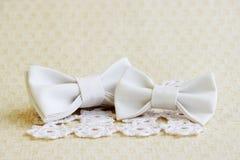 在正方形的米黄蝴蝶领带编织了白色餐巾和一只小蝴蝶在一个发带在米黄背景 时尚accessori 免版税库存图片