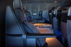 在正确的业务分类飞机的软的扶手椅子 在业务分类飞机的开放舷窗 免版税库存照片