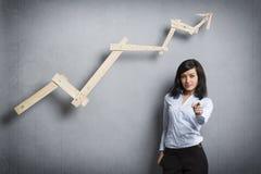 在正面趋向图表前面的成功的女实业家 免版税库存照片