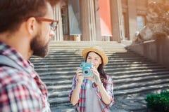 在步的好和beautfiul年轻女性旅游立场和拿着蓝色照相机 她拍她的男朋友和神色的照片 库存图片