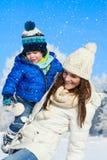 在步行在晴朗,冬日-雪落的愉快的家庭 免版税库存照片