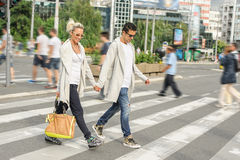 在步行斑马线的时兴的夫妇横穿路 库存照片