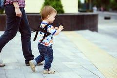 在步行期间,妈妈保险她的孩子 免版税库存照片