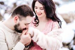 在步行的年轻夫妇在多雪的山 库存照片