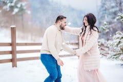 在步行的年轻夫妇在多雪的山 免版税库存图片