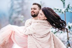 在步行的年轻夫妇在多雪的山 库存图片