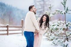 在步行的年轻夫妇在多雪的山 图库摄影