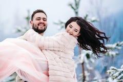 在步行的年轻夫妇在多雪的山 免版税图库摄影