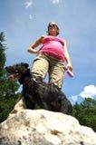 在步行的怀孕的woam与她的狗 免版税库存照片
