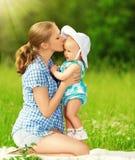 在步行的愉快的家庭。亲吻婴孩的母亲 免版税图库摄影